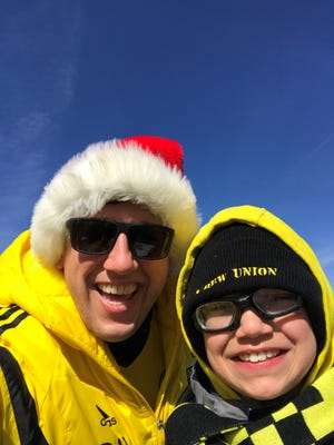 Benjamin Lanka, left, poses with his son, Cooper, for the Columbus Crew season opener in March, known to fans as Crewsmas.