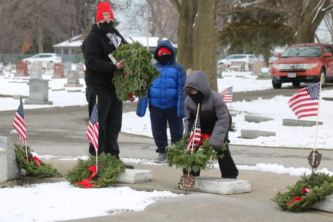 Volunteers place wreaths at the gravesites of veterans at Riverview Cemetery in Port Clinton while wearing masks and maintaining social distancing as a part of Wreaths Across America on Saturday.