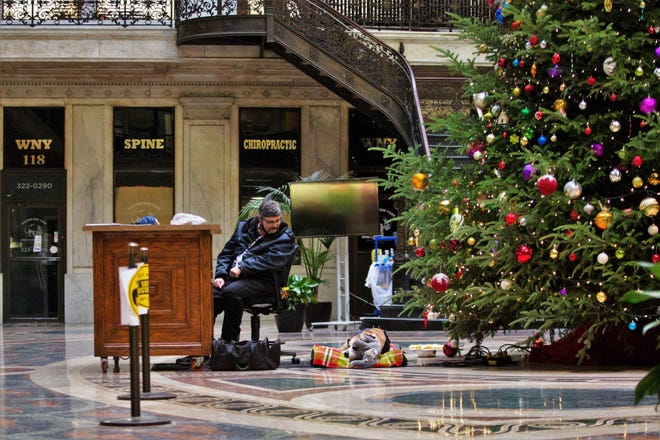 Mark Fermo, a security guard who works for Ellicott Development, watches as his dog Mercedes lays on her bed at the Ellicott Square Building in Buffalo on Wednesday, Dec. 9, 2020.