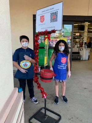 Jordan and Sophie ring the kettle bell in Ventura in memory of their grandmother Teresa, who was a longtime bellringer for The Salvation Army.