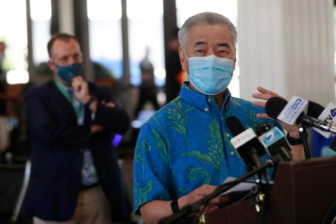 In this Oct. 15, 2020 file photo, Hawaii Gov. David Ige speaks at a news conference as Lt. Gov. Josh Green, left, looks on at the Daniel K. Inouye International Airport in Honolulu.