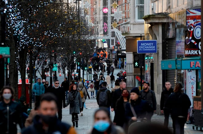 Pedestrians, some wearing a face mask or covering due to the COVID-19 pandemic, walk past closed shops in central London on December 20, 2020.