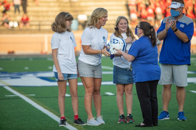 The family of late Assistant Principal Brian Dietz is given a helmet in his honor before a high school football game between North Oconee High School and Oconee County High School in Watkinsville, Ga. on Friday, Sept. 4, 2020. The Oconee County Warriors won 27-7. (Photo/Jenn Finch, Athens Banner-Herald)