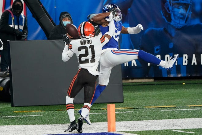 Browns cornerback Denzel Ward (21) defends New York Giants' Darius Slayton (86) during the first half of the Browns' 20-6 win on Sunday night. Ward returned after missing three games with a calf injury and played a key role in the victory. [Seth Wenig/Associated Press]
