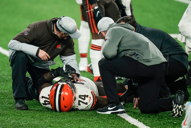 Trainers check on Browns offensive guard Chris Hubbard (74) during the first half of Sunday night's game against the New York Giants. Hubbard is out for the season with a knee injury and rookie Nick Harris is expected to start at right guard on Sunday against the New York Jets. [Seth Wenig/Associated Press]