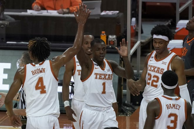 Texas' Andrew Jones (1) is congratulated by teammates, including Greg Brown (4), after making a three-point basket against Oklahoma State during the first half of an NCAA college basketball game in Austin, Texas, Sunday, Dec. 20, 2020.