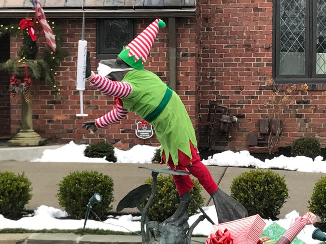 The popular bronze frog statue outside a River Road residence reflects both the season and 2021 optimism in its latest costume. Along with the elf's suit, the frog's webbed hand holds a vaccination needle, marked Pfizer.