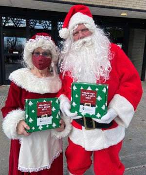 """Santa and Mrs. Claus prepare to distribute boxes of goodies and virtual experiences Saturday at """"Breakfast With Santa."""""""