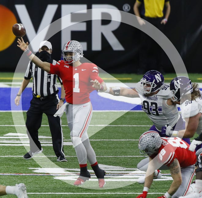 Ohio State Buckeyes quarterback Justin Fields (1) throws a pass while being grabbed by Northwestern Wildcats defensive lineman Joe Spivak (93) during the second quarter of the Big Ten Championship football game at Lucas Oil Stadium in Indianapolis on Saturday, Dec. 19, 2020. Ohio State won 22-10.