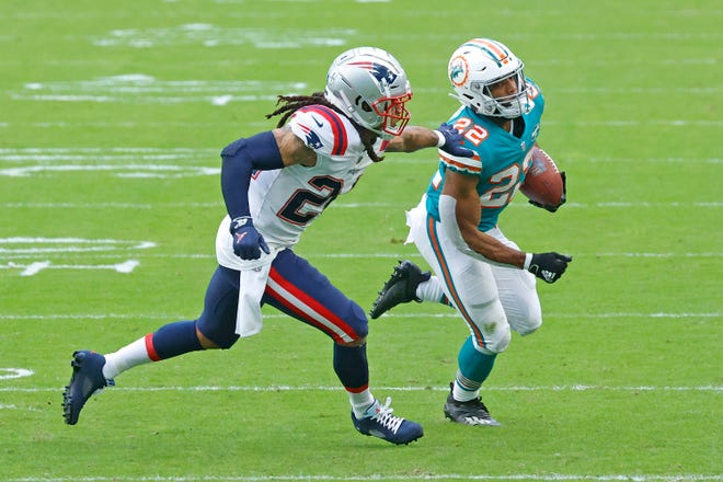 New England Patriots cornerback Stephon Gilmore (24) defends against Miami Dolphins running back Matt Breida (22) during Sunday's game in Miami Gardens, Fla.