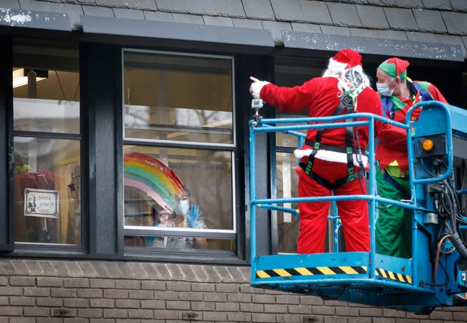 """Santa Claus waves to patient Emma from a cherry picker outside Leeds Children's Hospital in Leeds, England, on Monday. """"Operation Airborne Santa"""" transported him to all four floors of the hospital to talk to patients from a safe distance."""
