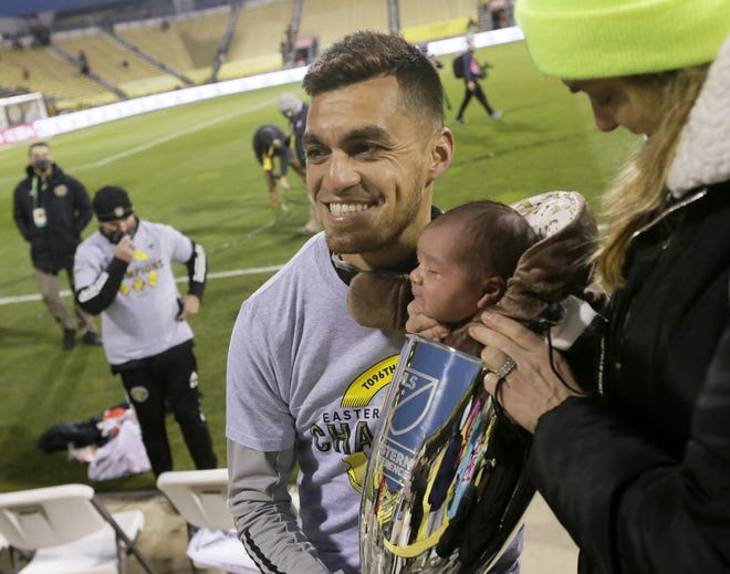 Hector Jimenez holds his two-week-old son, Mateo, after the Crew defeated the New England Revolution in the MLS Eastern Conference final on Dec. 6 in Mapfre Stadium.