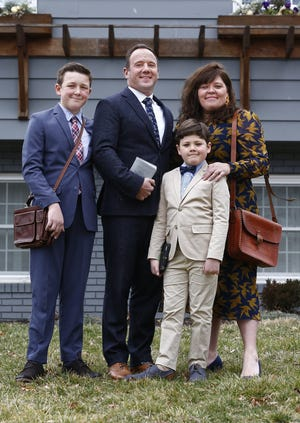 The Richards are Jehovah's Witnesses. The family has been making calls and writing letters instead of going door-to-door or greeting people in public due to the pandemic. Posing in front of their home are, from left: son Harrison, 12; dad Steve, 41; son Finn, 8; and mom Amber, 38.