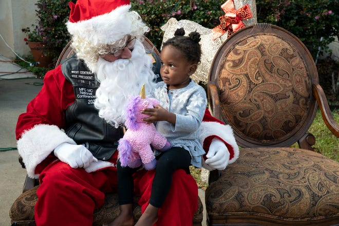 Santa gives a girl a gift at the Carpenter's House for Children in Leesburg on Sunday. [Cindy Peterson/Correspondent]