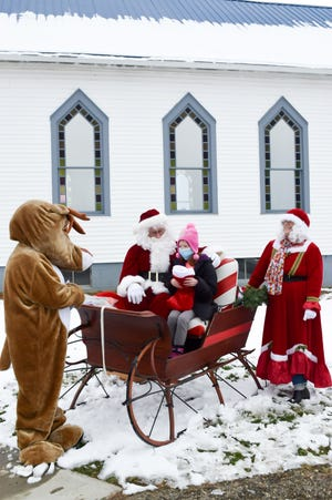 Rylee Lenarz tells Santa (Norm Gonder) her Christmas list, as Rudolph (Pastor Dee Ryan) and Mrs. Claus (Nancy Gonder) watch. The group passed out stockings at their church, Abundant Blessings, in Cambridge.