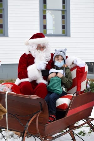 Santa reminds Logan Lenarz to be good this year. Norm Gonder played the role of Santa at the Abundant Blessings Church on Cadiz Road in Cambridge. The church handed out stockings and holiday cheer to anyone who stopped by.