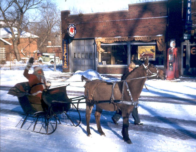 Monmouth's longtime Santa, Dr. Cudd is pictured in a sleigh drawn by a mule with deer antlers tied to its head in a 1945 Christmas parade on South Main Street. The photo was taken in front of Thompson Motors, which today houses Columbia Decorating. [Photo by Paul Kobler]