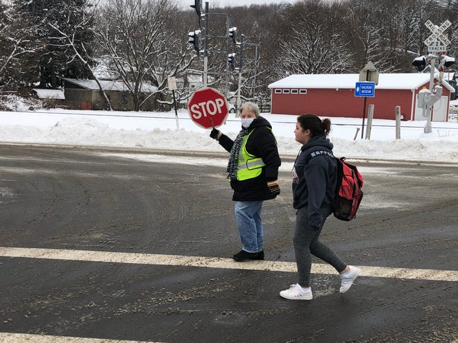 Working her final after school shift on Friday, Dec. 18, crossing guard Donna Larnard stops traffic so a Hornell Intermediate School student can safely cross the intersection.