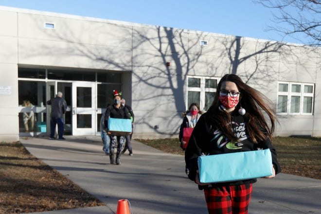 Addi Anderson, 13, president of the West Burlington Junior High Student Council, helps load boxes of food collected for the student council's Christmas food drive Monday in West Burlington.