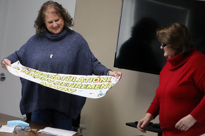 Mary Beaird, the outgoing director of the Southeast Iowa Regional Airport, is presented with a banner from her replacement, Sara Sandburg, Dec. 18 during her final airport authority board meeting as director in the boardroom.