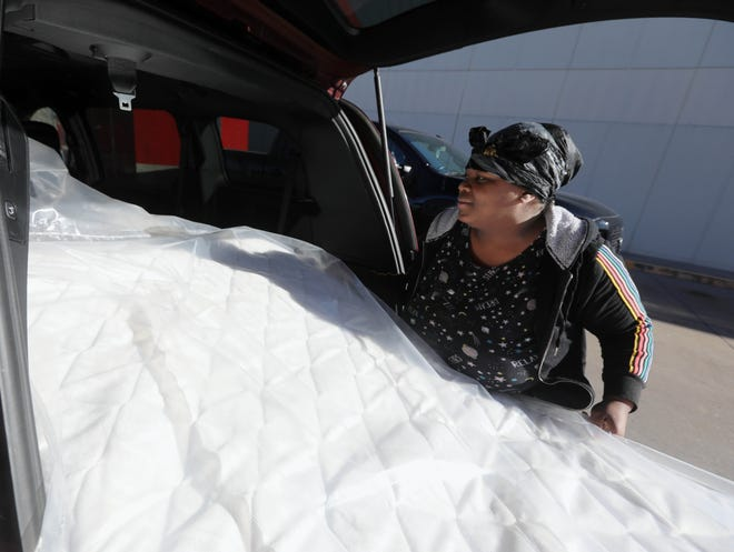 Yaisha Marshall loads one of two mattresses into the back of a minivan Monday during Slumberland Furniture's Homes for the Holidays program at the Burlington furniture store. The local store donated 14 mattresses with frames and box springs to area families in need. Slumberland Furniture was donating 2,500 beds across 12 states. Since 1993, through the 40 Winks Foundation and Homes for the Holidays donation event, Slumberland Furniture given away more than 45,000 beds.