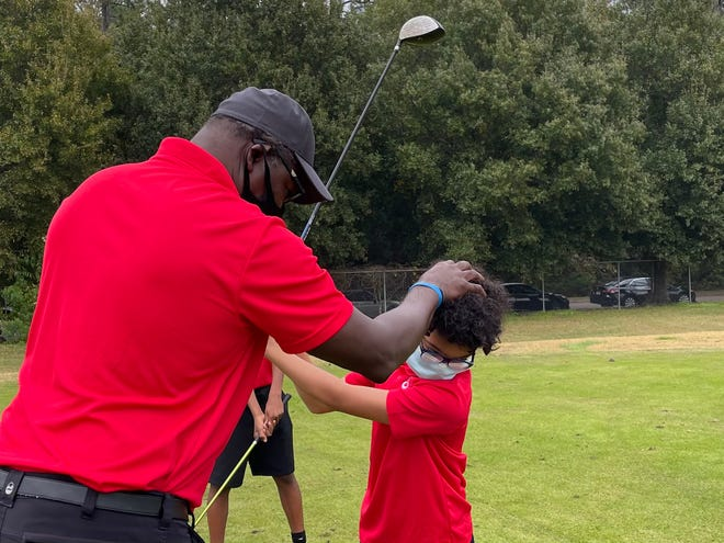 Long-time First Tee coach Robert Young helps William Lyles with his head position during a recent practice session at the Brentwood Golf Club