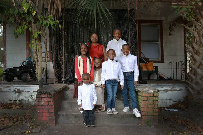 Mary Kinney with grandchildren (from left) Jade, 7, Jacob, 3, Aamilah, 5, King, 6, Karron, 11, and Tyree, 9. Kinney, 50, who works with autistic children at Sallye B. Mathis Elementary School, has adopted six of her grandchildren who were being neglected by their parents.