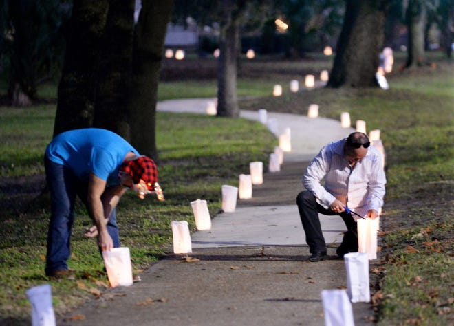 Volunteers Dan Hutton and Al Sherman light candles inside the bags to illuminate the path for others off Park Street for Sunday's 36th annual Riverside-Avondale Luminaria.