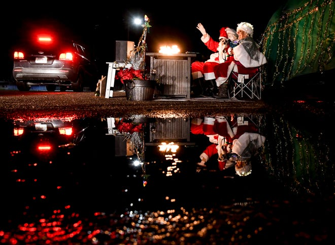 """Santa Claus, a.k.a. Kent Carroll, and Mrs.Claus, a.k.a. Patti Peitz-Carroll, wave at passing motorists while sitting by a firepit Saturday on the Finney County Fairgrounds exhibition parking lot during the """"A Very COVID Christmas Reverse Parade of Lights"""".  The event, held by the Finney County Convention and Visitors Bureau, provided a static parade of lit floats and other entries with motorists driving by while staying in their vehicles for COVID-19 precautionary measures."""
