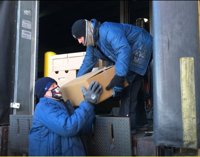 Bill Green, left, and Chad Strong unload a donation of turkeys and hams from Ruiz Foods last week. The donation of 144 turkeys and 85 hams will support seven local non-profits in the area to provide meals to families and individuals this holiday season.