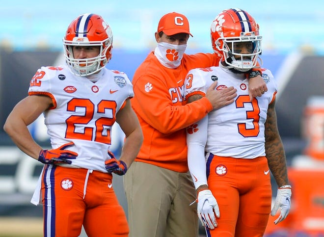 Clemson coach Dabo Swinney, center, hugs wide receiver Amari Rodgers, right, during warm-ups before the ACC title game on Dec. 19. [Jeff Siner/The News & Observer via AP]