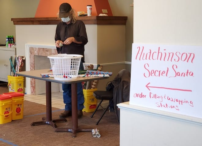 A volunteer wraps presents in the Hutchinson Regional Medical Center Annex (former Dillon Living Center) in preparation for the annual Hutchinson Secret Santa distribution. More volunteers are needed to wrap and deliver toys and this year, organizers are seeking more names of children to receive them.