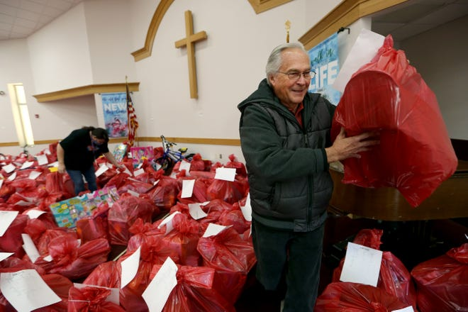 Volunteer Ken Willard carries a gift bag out to a family, Monday morning, from the sanctuary in the Salvation Army Center with Doretta Dickson, left, during the first day of distribution to pre-registered families.