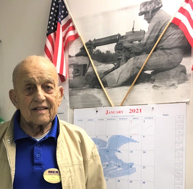 "Retired U.S. Marine Corps Sgt. Maj. Marion ""Cass"" Carcirieri poses for a photo at his office on Camp Geiger next to a picture of him with his weapon of choice, a .30 caliber water-cooled machine gun, circa 1955."