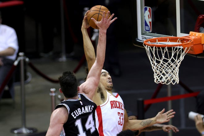Houston Rockets' Brodric Thomas (33) dunks ahead of San Antonio Spurs defender Drew Eubanks (14) during the fourth quarter of an NBA basketball game in Houston, Thursday, Dec. 17, 2020. (Carmen Mandato/Pool Photo via AP).