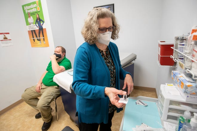 Director of Nursing Kathleen Napier prepares a dose of the COVID-19 vaccine for Help Desk Analyst Aaron Harris on Wednesday, Dec. 16, 2020, at the Cabell-Huntington Health Department in Huntington, W.Va.