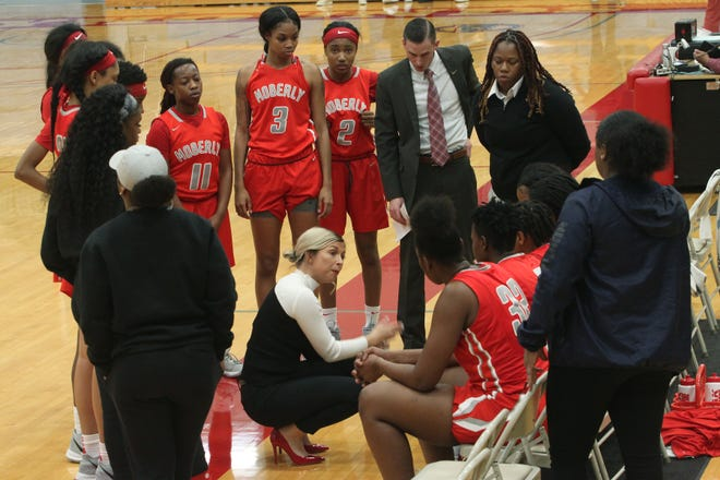 Moberly Area Community College women's head coach Hana Haden squats as she gives instructions to her seated players during a time out of a home basketball game played in the 2019-20 season. Among the team members shown standing are No. 11 Kori Tomlin, No. 3 Makira Webster and No. 2 Bryce Dowell, and assistant coaches Dustyn Yung and Jalisa Mitchell.