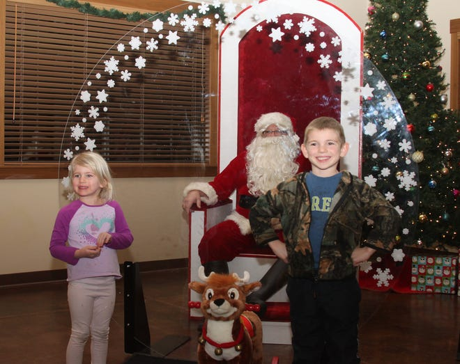 The COVID pandemic could not keep one of Santa Claus from visiting with children at The Lodge in Rothwell Park during the Moberly Altrusa Club's annual Christmas Lights in the Park festival. A large plexiglass window separates Santa from children as a precautionary measure as they visit him Saturday. Joining Santa, also known as Steve Calcagno, are siblings Harper, 4, and Easton, 5,  children of Philip and Alisa Grubaugh of Huntsville.