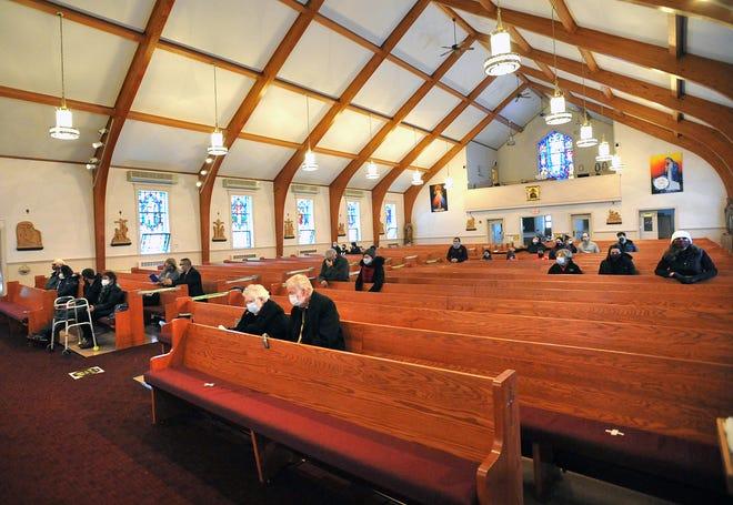 Parishioners sit socially distanced during Mass at Resurrection Parish in Hingham, Sunday, Dec. 20, 2020.