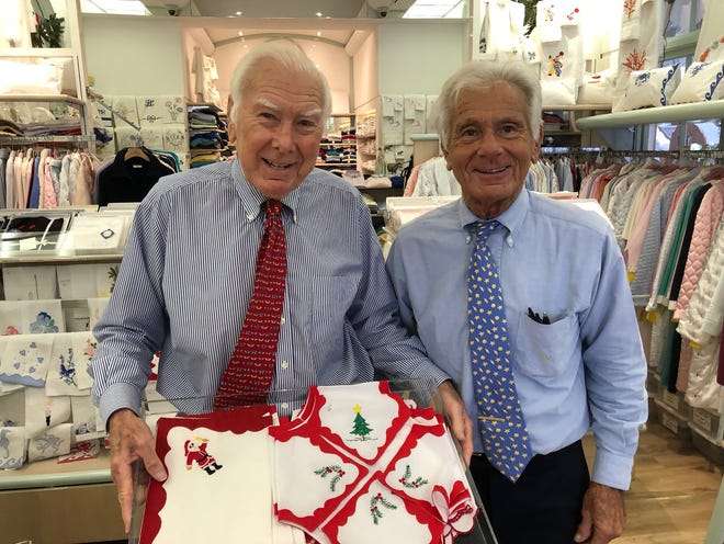 Brothers Edward and Robert Kassatly display Christmas-theme linens in Kassatly's, their iconic store on Worth Avenue in Palm Beach.