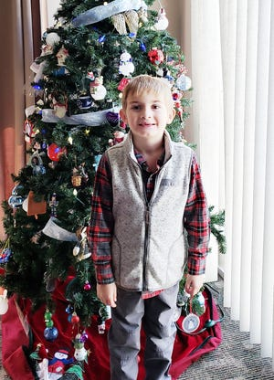 Regan James Charles Nolan, who turns 6 today, waits by the tree for a combination of birthday and Christmas gifts. The son of Joe and Rochelle Nolan of Pontiac will have two more days to wait for Christmas.