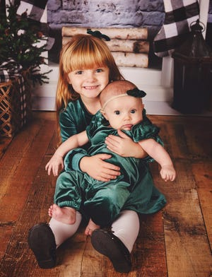 Ashtyn Rich, 4, holds little sister Annie, 4 months, by the fireplace in anticipation of Christmas. They are the daughters of Phillip and Devyn Rich of Pontiac.