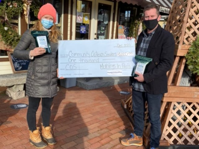 Mornings in Paris Owner Paul Humphrey presents a check for $1,000 to Community Outreach Services Development Director Michelle Allen recently after raising the funds, pound by pound, from selling their specially roasted coffee beans over the last  eight months.