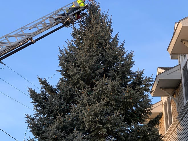 Chandler Hutchins places the star on top of the 40-foot spruce at Partridge House Assissted Living and Oceanside Center. Courtesy photo.