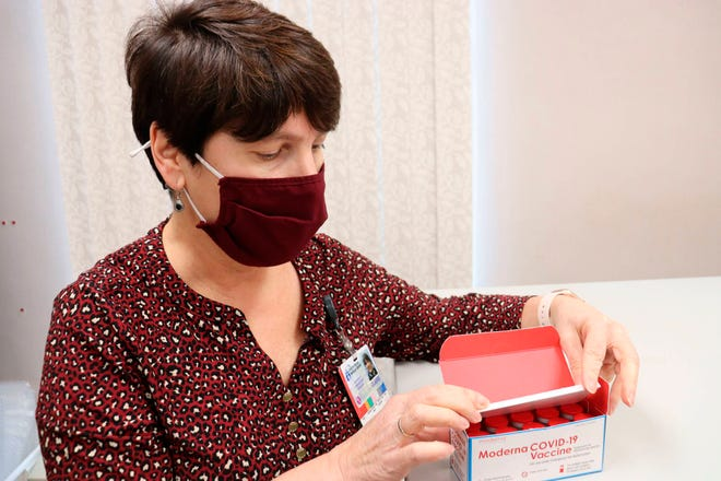 Claire McDonough, pharmacy operations manager at Central Maine Healthcare, opens a box of Moderna COVID-19 coronavirus vaccines in Lewiston, Maine on Monday, Dec. 21, 2020, after receiving 600 doses at the Central Maine Medical Center.