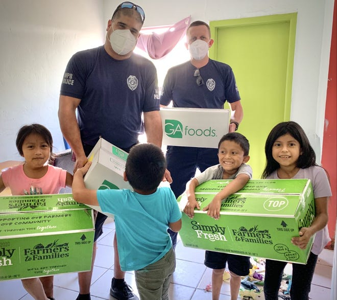 West Palm Beach police officers Angel Vargas, left, and Seth Buxton delivered thousands of meals and toys in 2020. COURTESY SETH BUXTON
