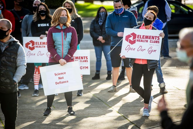 "Supporters at the Open Our Gyms Rally hold signs Monday from Elements Health Clubs at Wayne Morse Free Speech Plaza in downtown Eugene. ""Science Not Defiance"" on the signs refers to the data that shows gyms have not been significantly contributing to the spread of COVID-19."