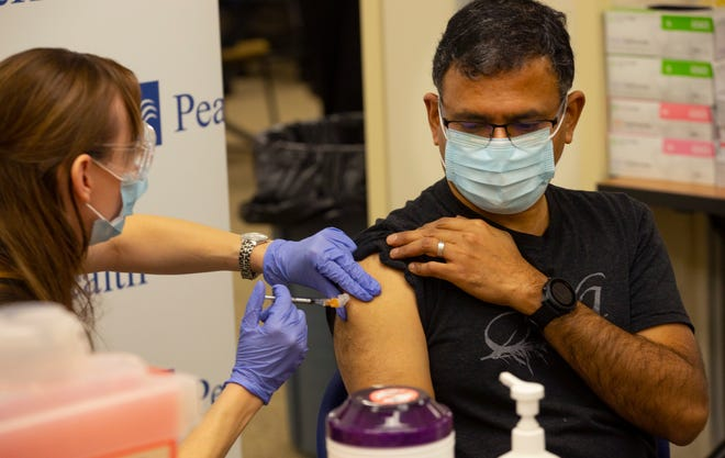Dr. Karthik Mahadevan, right, receives a vaccination for the coronavirus from Registered Nurse Cassandra Antosz, left, during a vaccination clinic at Sacred Heart RiverBend Hospital in Springfield Monday Dec. 21, 2020.