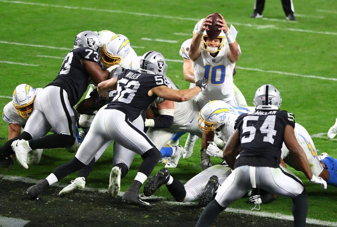 Los Angeles Chargers quarterback Justin Herbert (10) dives into the end zone for the game-winning touchdown run in overtime in a 30-27 win over Las Vegas Raiders on Dec. 17.