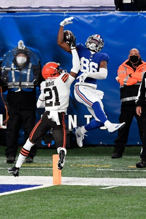 New York Giants wide receiver Darius Slayton (86) cannot complete the pass with pressure from Browns cornerback Denzel Ward (21), Sunday, Dec. 20, 2020, in East Rutherford, N.J.
